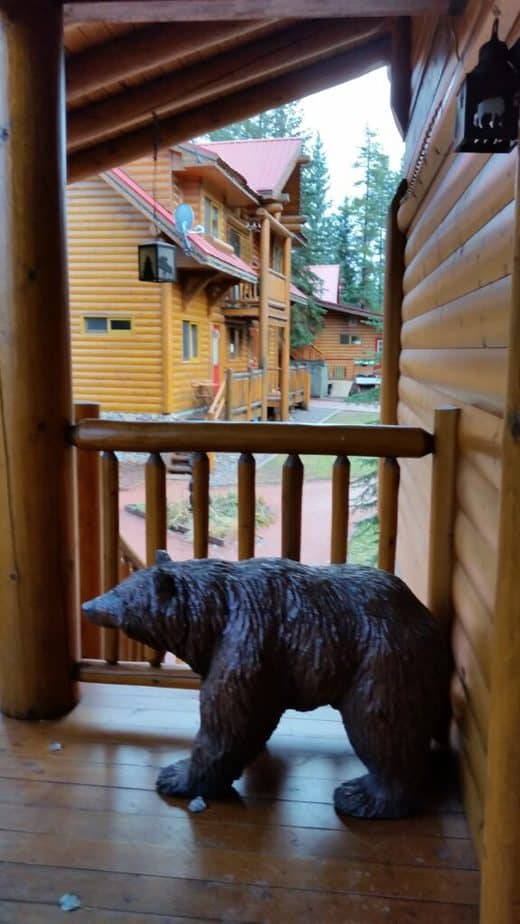 A carving of a bear on the patio of a log cabin in Lake Louise