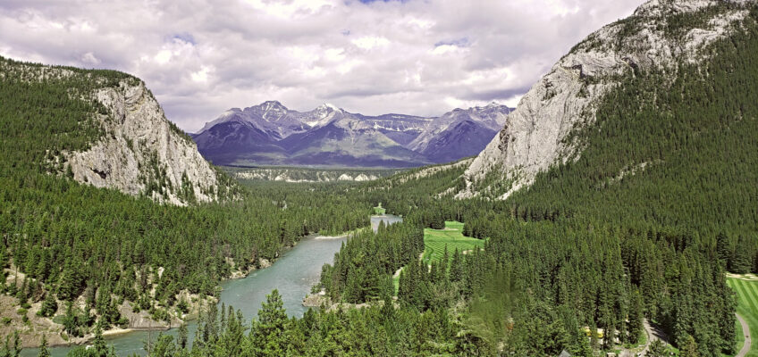 A sweeping view of the Bow Valley with green mountainsides along the Bow River